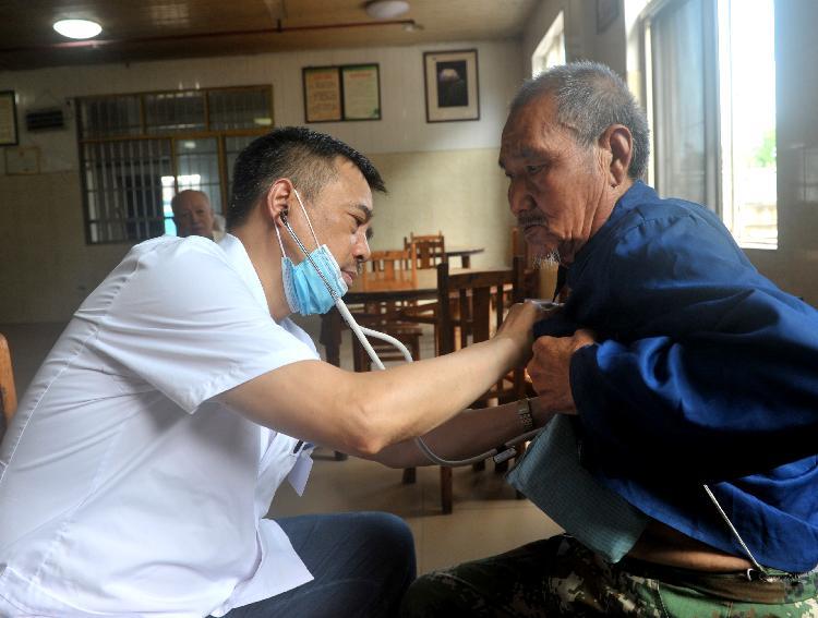 ▲主任医师黎成禄给养老院老人诊断病情并免费开了药物.jpg